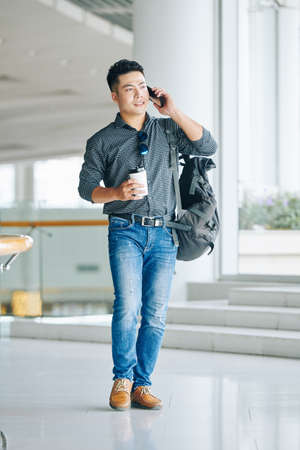 Handsome serious young Asian man with coffee cup in hands walking in airport terminal and talking on phone