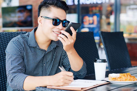 Smiling young man recording voice message for friend or coworker when having breakfast and working at cafe table