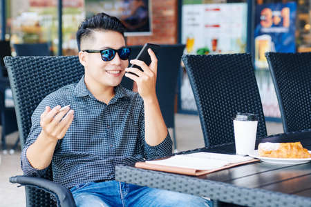 Smiling Asian businessman sitting at cafe table and recording voice message to explain work to colleague