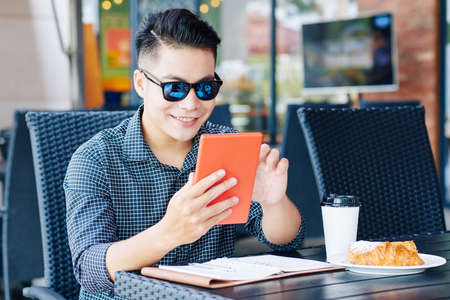 Positive handsome young man using application on tablet computer when having cooffee and croissant in cafe Banco de Imagens