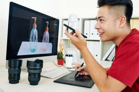 Cheerful creative Vietnamese photographer retouching photo of glass bottles on computer screen and recording voice message