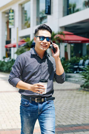 Portrait of positive young Asian man walking in the street, drinking take away coffee and calling on phone
