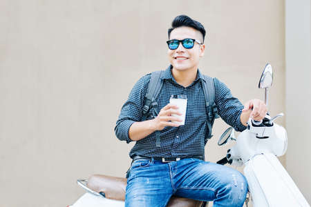 Handsome positive young man in sunglasses sitting on scooter outdoors and drinking delicious taje away coffee