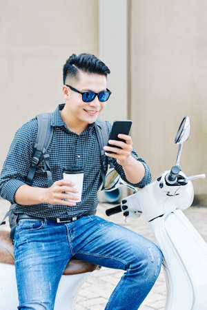 Smiling cool young Asian man sitting on scooter, drinking coffee in disposable cup and reading text messages in his smartphone