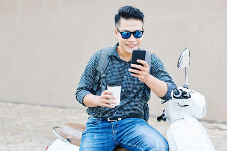 Smiling young man with coffee cup sitting on scooter and checking notifications in his smartphone