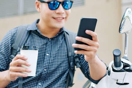 Cropped image of positive young Asian man reading text messages on smartphone when sitting outdoors