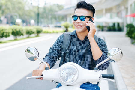 Smiling happy young Asian man in sunglasses riding on scooter and calling on phone