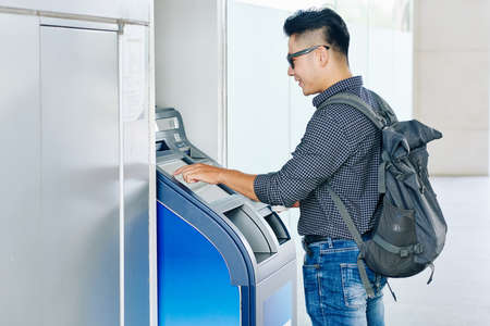 Smiling young Asian man entering pin code in ATM cash terminal to withdraw money