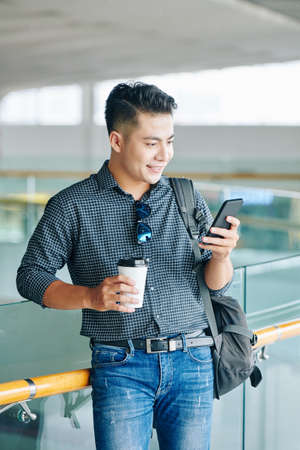 Smiling young Vietnamese man with backpack standing in airport terminal, drinking coffee and checking schedule in smartphone Banco de Imagens