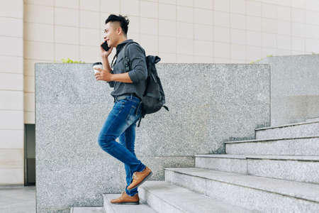 Smiling young Asian man with backpack walking down the stairs in the street and calling on phone