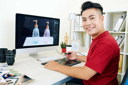 Cheerful young Vietnamese professional 3D designer working on graphic tablet on visualization for commercial project Banque d'images