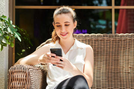 Pretty young woman in white sleeveless blouse sitting outdoors and smiling when reading text messages in her smartphone