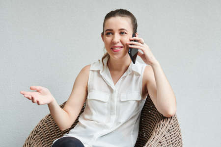 Portrait of young positive female entrepreneur actively gesturing when talking on phone with coworker Banco de Imagens