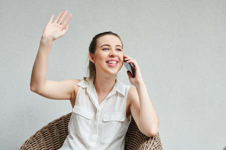 Young pretty businesswoman talking on phone and waving with hand to bring attention of coworker or friend