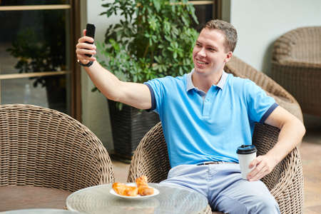 Handsome smiling young man taking selfie in outdoor cafe when having coffee with croissants for breakfast