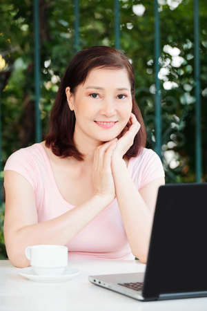 Portrait of positive mature female freelancer sitting at cafe table with cup of coffee and working on laptop