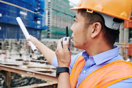Contractor using walkie-talkie for communication with other workers when managing processes at construction site Banco de Imagens