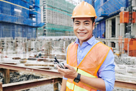 Portrait of cheerful Vietnamese construction engineer standing with portable radio communicator and smiling at camera Stock fotó