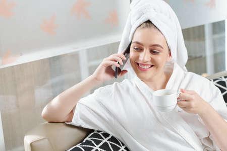 Fijne mooie jonge vrouw in badjas die koffie drinkt en de telefoon opneemt na een behandeling in de spasalon