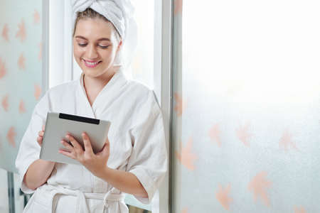 Pretty smiling young woman in bath robe leaning on wall and reading article on table computer Stock Photo