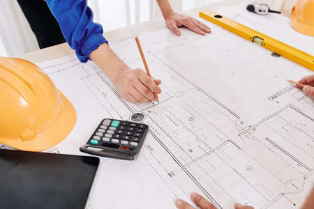 Hands of contractor in blue overall leaning on table and examining building blueprint to plan work for upcoming week Stock Photo