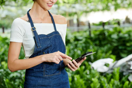 Cropped image of nursery garden manager using nfs device attached to smartphone when entering sum of payment for flowers and plants