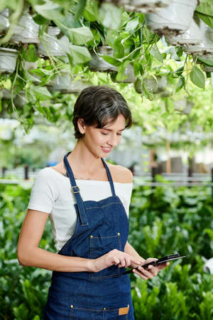 Smiling female nursery garden owner using nfs device attached to her phone to accept payment from customer