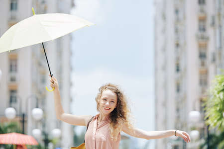 Happy young pretty woman walking in the street with umbrella in hand on windy day