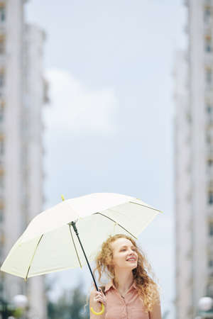 Beautiful young Caucasian woman with big white umbrella walking in city