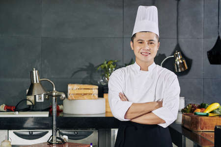 Portrait of Asian young chef standing with arms crossed and smiling at camera while standing in the kitchen