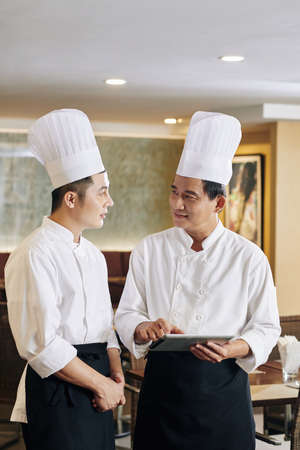 Asian mature chef in uniform holding tablet pc and explaining working moments to his student while they standing at the restaurant