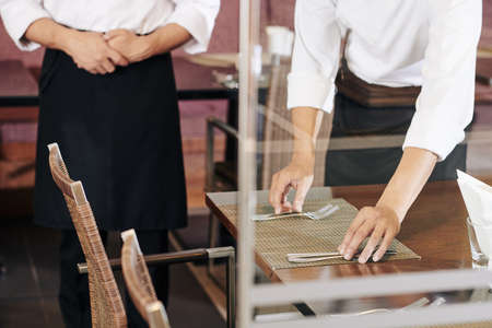 Close-up of waiter serving the table he putting knives and forks on the table with manager standing near by at the restaurant