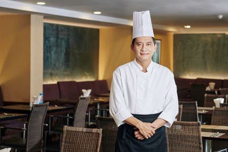Portrait of Asian mature chef in uniform and in hat looking at camera while standing at empty hall of the restaurant