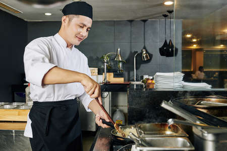 Asian young chef standing near the stove and cooking rice for special dish in the kitchen of the restaurant