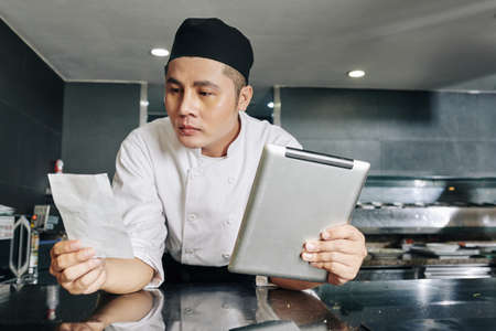 Asian young chef reading recipe of new dish and using digital tablet while standing in the kitchen Stok Fotoğraf