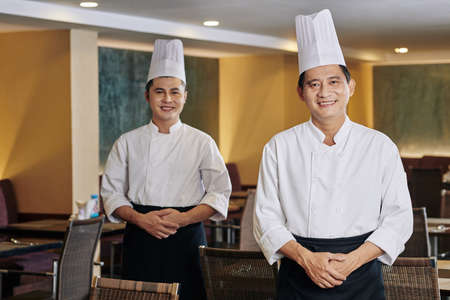 Portrait of Asian mature chef in uniform smiling at camera while standing with his colleague in the background at the restaurant
