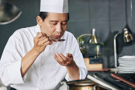 Asian mature cook in uniform holding spoon and tasting his dish in the kitchen of the restaurant