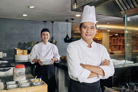 Portrait of confident Asian chef standing with arms crossed and looking at camera with young cook preparing food in the background in the kitchen