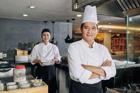Porträt eines selbstbewussten asiatischen Kochs, der mit verschränkten Armen steht und die Kamera mit einem jungen Koch ansieht, der im Hintergrund in der Küche Essen zubereitet