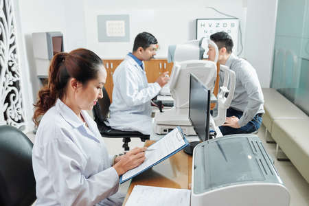 Asian nurse in white coat sitting at the table and filling the medical card while doctor examining the patient in the background at hospital