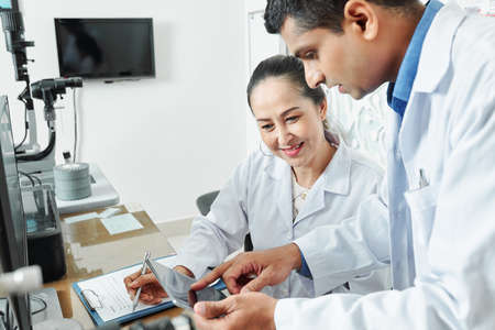 Indian male doctor pointing at digital tablet and talking to his Asian colleague while they working in team at the table at office 版權商用圖片