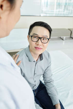 Young Asian man in eyeglasses looking at his doctor and listening to her recommendations during his visit at hospital