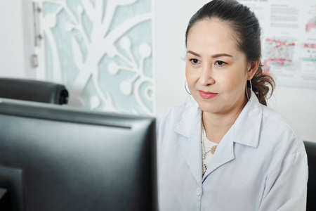 Asian mature female woman looking at computer monitor while working at her workplace at office