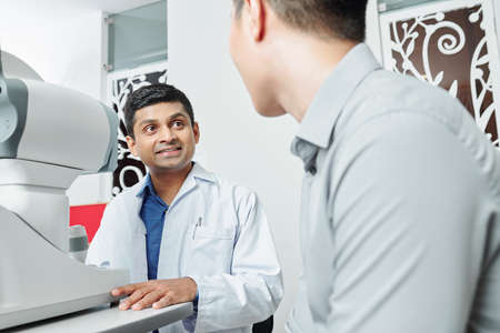 Indian doctor in white coat sitting at the table in front of medical equipment and talking to the patient during his visit at office