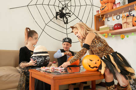 Group of friends sitting on sofa and dividing candies after played trick or treat at Halloween party at home Stock fotó