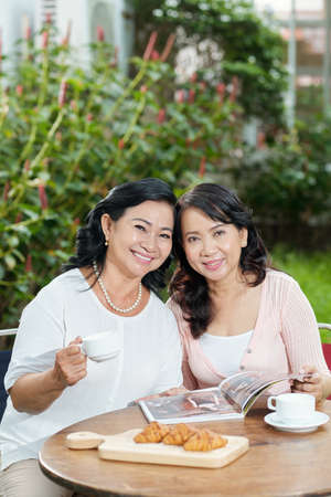Portrait of happy Asian mother with her daughter smiling at camera while sitting at the table and drinking coffee outdoors