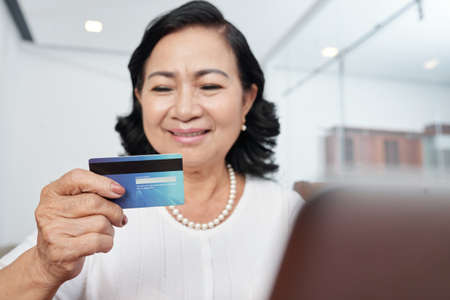 Asian senior woman looking at her credit card in her hand while sitting at the table in front of laptop