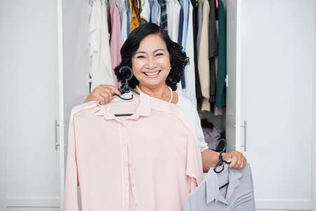 Portrait of Asian senior woman smiling at camera while making a choice between two blouses at home Фото со стока