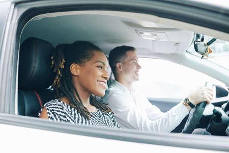 Glückliche Afrikanerin, die in der Nähe des jungen Mannes sitzt, der ein Auto fährt, das sie fährt und lächelt