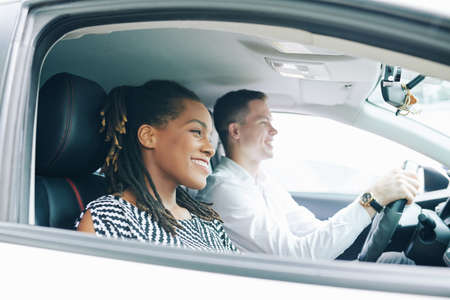 Happy African woman sitting near the young man who driving a car they driving and smiling Фото со стока
